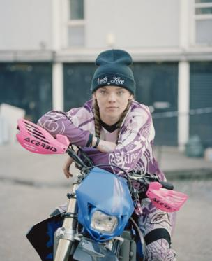 A young girl on a motorcycle