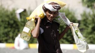 رجل يمني يحمل مساعدات غذائية قدمتها له منظمة خيرية محلية في العاصمة صنعاء