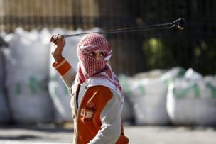 جوان فلسطینی در اعتراض به تصمیم دونالد ترامپ سنگ پرتاب میکند