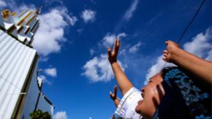 A woman raises her hand to the sky at the annual gathering of the Light of the World church.