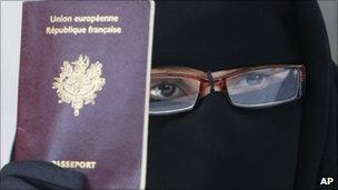 A Muslim woman in full face veil holds up her French passport at a conference near Paris, May 2010