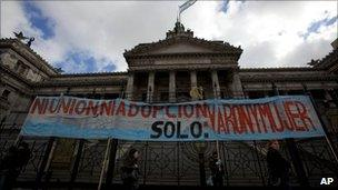 """Demonstrators hold a banner that reads in Spanish """"Neither union nor adoption. Only: men and women"""" outside Congress in Buenos Aires on 14 July"""