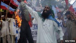 Supporters of Shabab-e-Milli burn an effigy of David Cameron in Karachi 31 July 2010