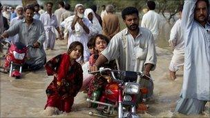 A man evacuates his children in Nowshera, Khyber-Pakhtoonkhwa Province.