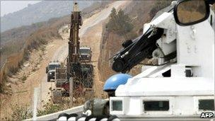 UN troops observe an Israeli military bulldozer along the border with Lebanon, 4 August