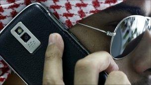 An Arabian man speaks on his BlackBerry
