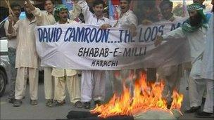Protesters burn an effigy of David Cameron