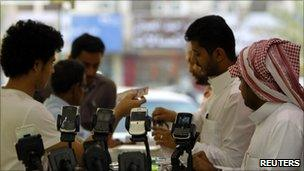 Men stand near BlackBerry phones on sale at a shopping mall in Riyadh