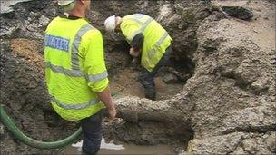 Workmen repairing the pipe