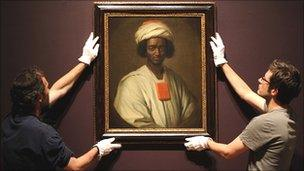 Employees at London's National Portrait Gallery with the painting of Ayuba Suleiman Diallo