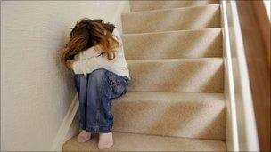 Child cowering on stairs