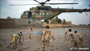Local residents scramble to recover water bottles dropped from a Pakistan Air force helicopter