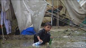 A child plays in the rain, Risalpur, Pakistan, 08/08