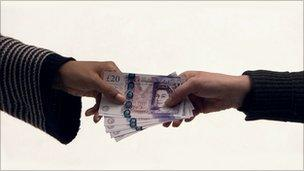 £20 notes being handed over