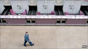Man walks past empty check-in desks at Glasgow airport