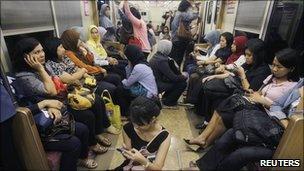 Women board a women-only carriage of a commuter train in Jakarta