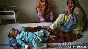Women alongside an ill child in Punjab province, Pakistan (23 August 2010)