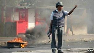 A policewoman by a burning tyre in Maputo, Mozambique (2 September 2010)