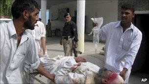 Pakistani volunteers carry an injured victim of a suicide bombing in Lakki Marwat on 6 September 2010