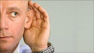 Man with his hand to his ear
