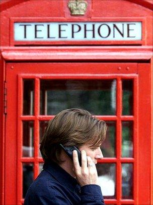 A mobile phone user makes a call while standing next to a BT payphone