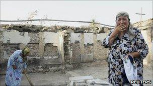 An Uzbek woman in the ruins of her house