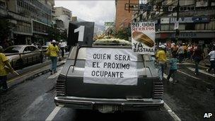 """A hearse with a poster that reads in Spanish """"Who will be the next occupant"""" and """"20,000 deaths is enough"""" during an opposition protest against violence in Caracas, in August"""