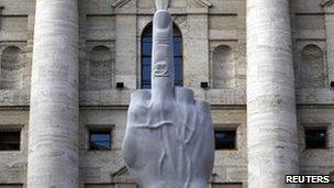 L.O.V.E. - a statue by controversial Italian artist Maurizio Cattelan - in front of the stock exchange in Milan