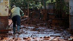 A Hungarian man cleans up after sludge spill in Devecser