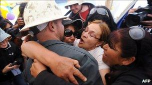 Relatives of the trapped miners hug a drill operator (9 October 2010)
