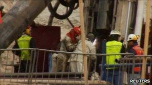 Engineers lower metal tubing into the mine shaft (10 Oct 2010)