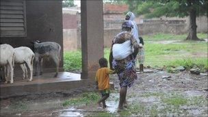 Woman wades through muddy fields with her children