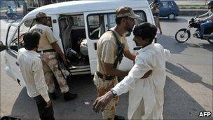 A Pakistani paramilitary soldier frisks a man in Karachi