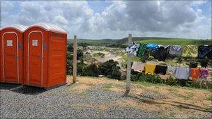 Temporary toilets and a washing line at the tent camp