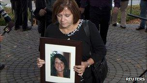 Roxanne Lloyd carrying a photograph of her daughter Jessica