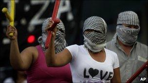 Masked demonstrators brandish batons during the protest in Buenos Aires