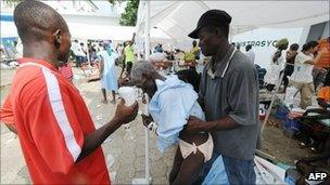 A man with fever is helped at a hospital in Saint-Marc, Haiti - 21 October 2010