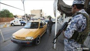An Iraqi policeman stands guard at a checkpoint in Baghdad