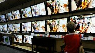 Customer looking at flat screen televisions on display in a store in California