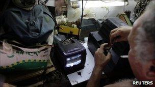 An electrician repairs a TV set in Havana