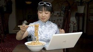 Young Chinese woman using a lap top in a restaurant