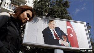 A woman passes a billboard of late President Haydar Aliyev