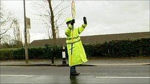 Lollipop lady stopping traffic