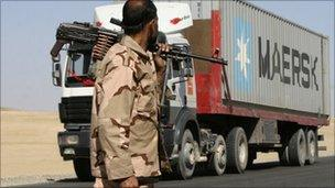 A private security contractor watches a Nato supply truck drive past in the province of Ghazni, south-west of Kabul, Afghanistan, Wednesday, Oct 27, 2010.
