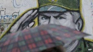 A woman with an umbrella walks past a mural of Gen Mladic in Belgrade, 26 October