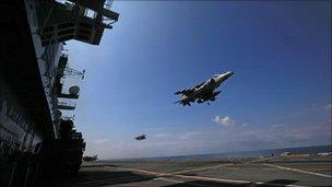 A Harrier jet hovers as it comes in to land on the flight deck of an aircraft carrier