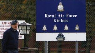 Royal Air Force personnel walk past a sign at the entrance to the RAF Kinloss airbase in Moray