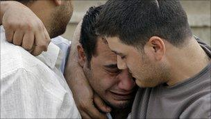 An Iraqi man is consoled by friends at a Catholic church in Baghdad, where dozens died on Sunday after gunmen attempted to take worshippers hostage