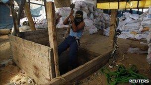 A Palestinian smuggler entering a tunnel running beneath the border with Egypt