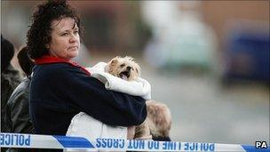 A woman with her dog at gas explosion scene in Salford, Greater Manchester